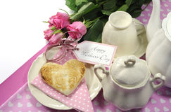 Pink theme Happy Mothers Day breakfast tray with copy space. Pink theme Happy Mothers Day breakfast in bed with tea cup and tea pot, roses and heart shape toast stock images