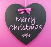 Pink theme Merry Christmas message. Greeting written on heart shape blackboard royalty free stock photos
