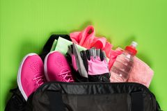 Pink things for sport and a bottle of water in a black bag on a green board. Pink things for sport and  a bottle of water in a black bag on a green board Stock Photo