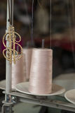Pink Thread in a Machine Spool Beside Dollar Sign Pendant Stock Image