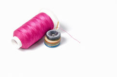 Pink thread with needle and buttons Royalty Free Stock Images