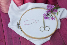 Pink thread and white fabric in the wooden embroidery frame for Royalty Free Stock Image