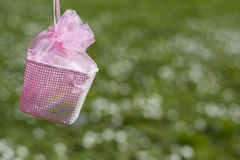 Pink tiny basket for Easter eggs handing in outdoors field of gr Royalty Free Stock Photos