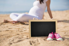 Pink Toddler sneakers and mini chalk board on the sand with pregnant woman on the background. A portrait of a pair of Pink Toddler sneakers and mini chalk board royalty free stock image