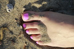 Pink toes resting on the beach Stock Photography