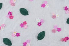 Pink tone paper flowers and green leaves pattern. On muslin fabric Stock Images
