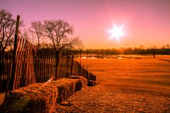 pink toned sunrise on the hill with a wood fence and straw bales stock images