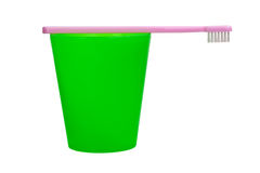 Pink toothbrush and green cup for children Royalty Free Stock Photo