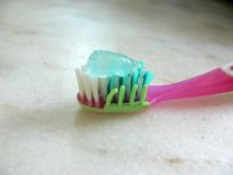 Pink toothbrush and paste. Toothpaste on pink toothbrush, light background Royalty Free Stock Photography