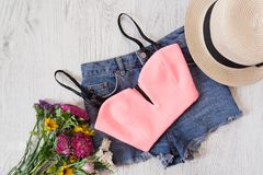 Pink top, denim shorts, hat and bouquet of wildflowers. Fashionable concept Royalty Free Stock Images