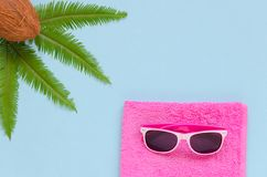 Pink towel, glasses, palm leaf, coconut over blue background. Summer or travel concept. Copy space composition royalty free stock photos