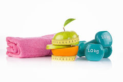 Pink towel, green apple with measuring tape with a pair of blue fitness dumbbells and protein drink. Healthy living, sports and diet concept Stock Photo
