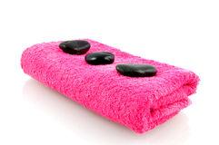 Pink towel with massage stones. Isolated on white background Stock Photos