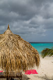 Pink Towels Under Thatched Hut and Stormy Skies Stock Photography