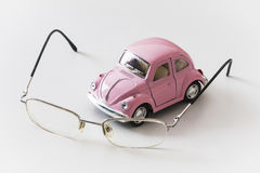 Pink toy car is on a white desk near the eyeglasses Stock Photo