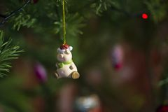 The pink toy - a mumps in a red cap with a green scarf hangs on a green New Year tree royalty free stock photo