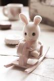 Pink toy rabbit sitting on rocking horse Stock Photo