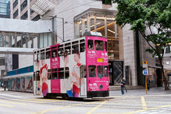 Pink Tram. A pink tram in Central, Hong Kong. Hong Kong trams, with colourful advertising, are the only double decker trams in the world and are one of the citys royalty free stock photo