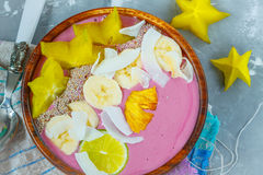 Pink tropical smoothie bowl carambola, pineapple, coconut.