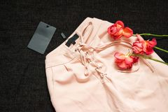 Pink trousers with drawstring on a black background, blank tag,. Roses. Fashion concept, close-up Royalty Free Stock Photography
