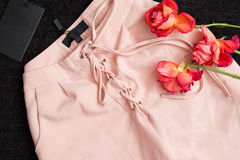 Pink trousers with drawstring on a black background, blank tag, roses. Fashion concept, close-up Royalty Free Stock Images