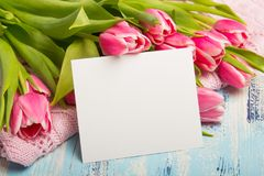 Pink tulip bouquet and balnk paper on blue wooden background,. Copy space. Beautiful flowers Stock Photo