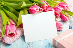 Pink tulip bouquet, gift box and balnk paper on blue wooden background,. Copy space Stock Photo