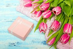 Pink tulip bouquet and gift box on blue wooden background,. Copy space. Beautiful flowers Royalty Free Stock Image