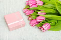 Pink tulip bouquet and small gift on light background,. Copy space Stock Photo