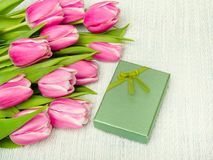 Pink tulip bouquet and small gift on light background,. Copy space Royalty Free Stock Photos