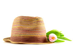 Pink tulip and colored straw hat. On a white background Stock Photo