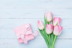 Pink tulip flowers and gift or present box on blue wooden table top view. Greeting card for Womans or Mothers Day. Flat lay. stock images