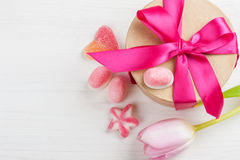 Pink tulip and gift box with red ribbon. Sweet hearts on a white painted wooden background. Top view with copy space Royalty Free Stock Photos