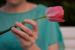 Pink tulip in the left woman hand. Gir in green dress l with jewelry on fingers holding a flower. Stock Image