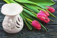 Pink tulips and an aromatic lamp on a wooden background Royalty Free Stock Image