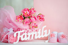 Pink tulips, baby shoes and family sign Stock Images