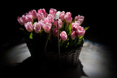 Pink tulips in the basket with wedding rings Royalty Free Stock Image