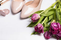 Pink tulips and beige shoes on white background Royalty Free Stock Images