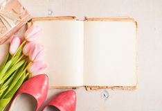 Pink tulips and blank book with women`s shoes over white wooden Stock Photos