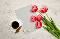 Pink tulips on a blank sheet of paper, mug of coffee and marshma Stock Images