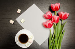 Pink tulips on a blank sheet of paper, mug of coffee and marshmallows, black wooden background. top view Stock Images