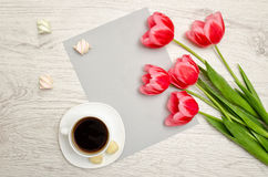 Pink tulips on a blank sheet of paper, mug of coffee and marshmallows, light wooden background. top view, space for text Stock Images