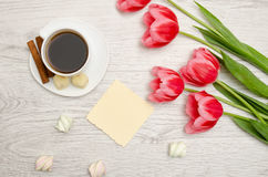 Pink tulips, blank sheet of paper, mug of coffee and marshmallows, light wooden background. top view Stock Images