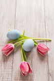 Pink Tulips and blue Easter Eggs From Above. On wood background Stock Photos