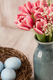 Pink Tulips and Blue Easter Eggs in a Nest. Pink tulips in a blue vase with blue Easter eggs in a nest Stock Images