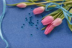 Pink tulips with blue ribbon on blue glitter background with copy space stock photos