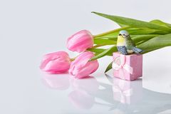 Pink tulips bouquet with gift box on a table royalty free stock images