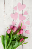 Pink tulips bouquet with paper hearts on wooden background Royalty Free Stock Images