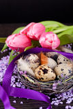 Pink tulips and brown eggs with purple ribbon easter decoration Stock Photo