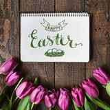 Pink, tulips bunch on dark barn wood planks background. Happy Easter brush nib lettering calligraphy. Pink, tulips bunch on dark barn wood planks background stock photo